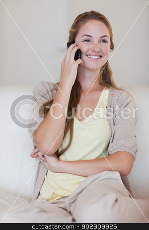 Smiling woman listening to caller on her cellphone stock photo, Smiling young woman listening to caller on her cellphone by Wavebreak Media