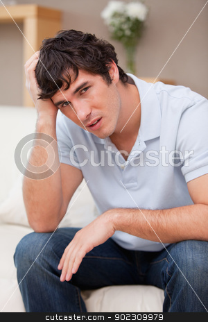 Despaired man sitting on the couch stock photo, Despaired young man sitting on the couch by Wavebreak Media