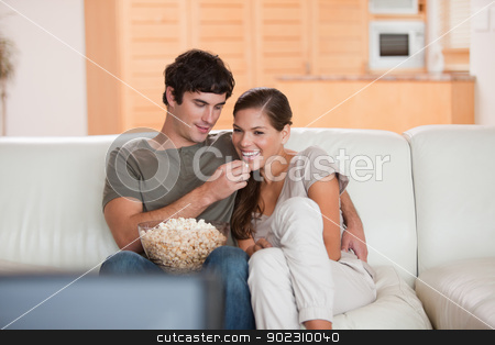 Couple on the couch watching a movie together stock photo, Young couple on the couch watching a movie together by Wavebreak Media