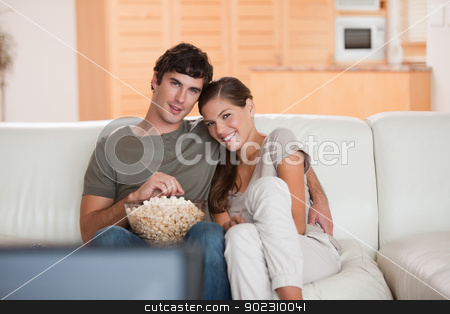 Couple with bowl of popcorn watching a movie on the sofa stock photo, Young couple with bowl on popcorn watching a movie on the sofa by Wavebreak Media