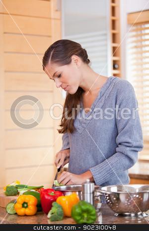 Woman in the kitchen preparing vegetables stock photo, Young woman in the kitchen preparing vegetables by Wavebreak Media