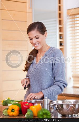 Smiling woman in the kitchen slicing vegetables stock photo, Smiling young woman in the kitchen slicing vegetables by Wavebreak Media