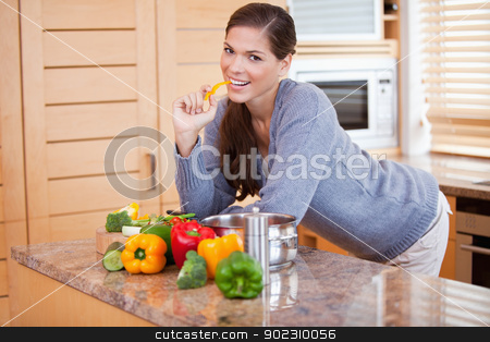 Smiling woman in the kitchen with vegetables stock photo, Smiling young woman in the kitchen with vegetables by Wavebreak Media