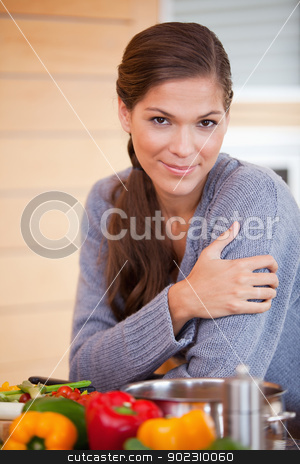 Woman leaning against the kitchen counter stock photo, Young woman leaning against the kitchen counter by Wavebreak Media