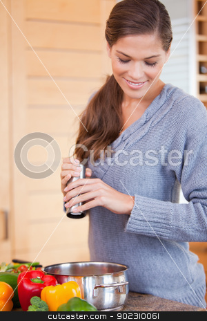 Woman adding spices to her vegetable stew stock photo, Young woman adding spices to her vegetable stew by Wavebreak Media