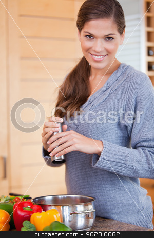 Smiling woman adding spices to her stew stock photo, Smiling young woman adding spices to her stew by Wavebreak Media