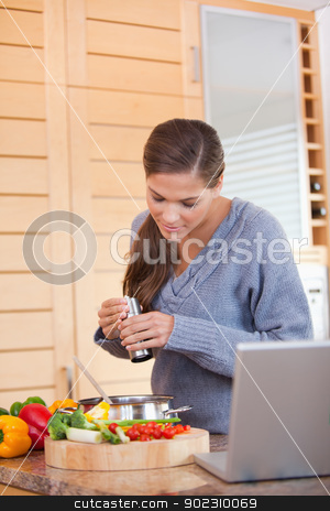 Woman spicing her meal stock photo, Young woman spicing her meal by Wavebreak Media