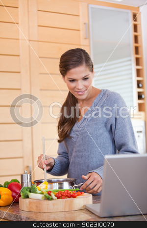 Woman reading off a recipe while cooking stock photo, Young woman reading off a recipe while cooking by Wavebreak Media