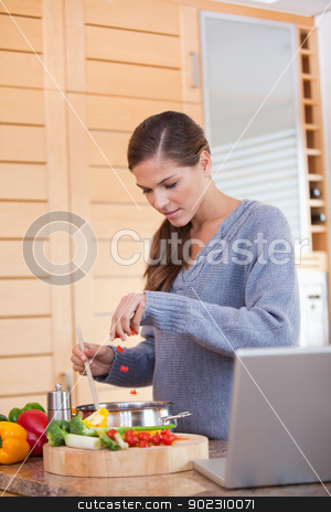 Woman adding carrot pieces to her stew stock photo, Young woman adding carrot pieces to her stew by Wavebreak Media