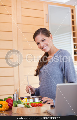 Smiling woman stirring the meal she is preparing stock photo, Smiling young woman stirring the meal she is preparing by Wavebreak Media