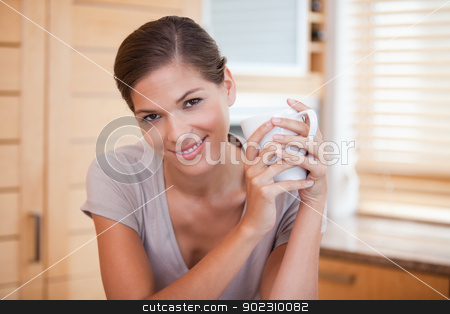 Smiling woman holding a cup in the kitchen stock photo, Smiling young woman holding a cup in the kitchen by Wavebreak Media