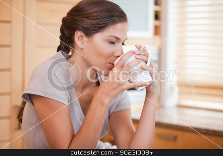 Side view of woman enjoying a cup of coffee stock photo, Side view of young woman enjoying a cup of coffee by Wavebreak Media