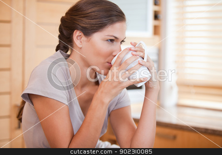 Side view of woman drinking coffee stock photo, Side view of young woman drinking coffee by Wavebreak Media