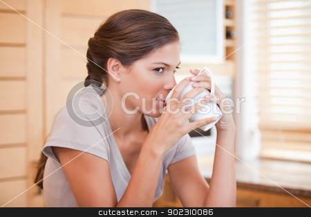 Side view of woman enjoying coffee stock photo, Side view of young woman enjoying coffee by Wavebreak Media