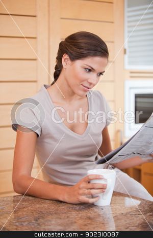 Woman reading newspaper while holding cup of coffee stock photo, Young woman reading newspaper while holding cup of coffee by Wavebreak Media