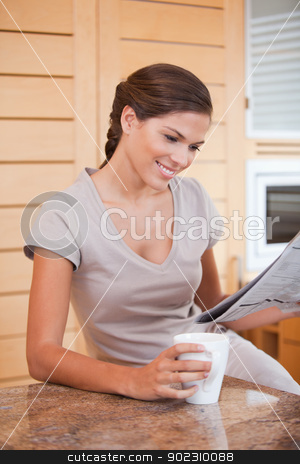 Smiling woman reading newspaper in the kitchen stock photo, Smiling young woman reading newspaper in the kitchen by Wavebreak Media