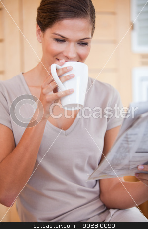 Woman taking a sip of coffee while reading newspaper stock photo, Young woman taking a sip of coffee while reading newspaper by Wavebreak Media