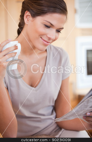 Woman reading newspaper while holding cup of tea stock photo, Young woman reading newspaper while holding cup of tea by Wavebreak Media
