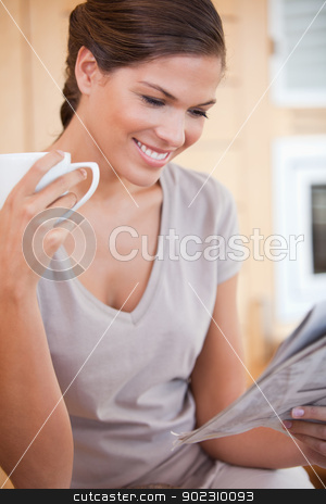 Smiling woman reading newspaper while having tea stock photo, Smiling young woman reading newspaper while having tea by Wavebreak Media