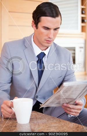 Man in suit making breakfast stock photo, Young man in suit making breakfast by Wavebreak Media
