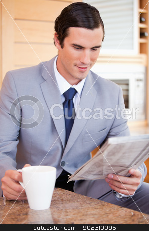 Businessman in the kitchen reading news and having coffee stock photo, Young businessman in the kitchen reading news and having coffee by Wavebreak Media