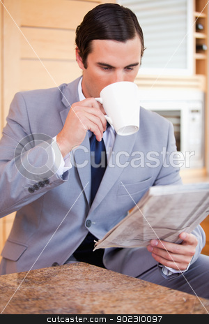 Businessman reading news and having a coffee stock photo, Young businessman reading news and having a coffee by Wavebreak Media