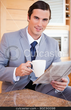 Businessman having coffee and reading news in the kitchen stock photo, Young businessman having coffee and reading news in the kitchen by Wavebreak Media