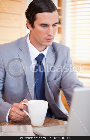 Businessman with coffee on his laptop stock photo, Young businessman with coffee on his laptop by Wavebreak Media