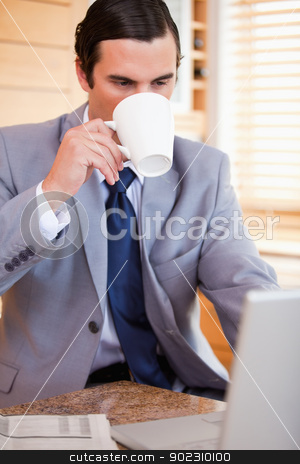 Businessman taking a sip of coffee next to his laptop stock photo, Young businessman taking a sip of coffee next to his laptop by Wavebreak Media
