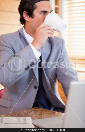 Businessman enjoying a cup of coffee in the kitchen stock photo, Young businessman enjoying a cup of coffee in the kitchen by Wavebreak Media
