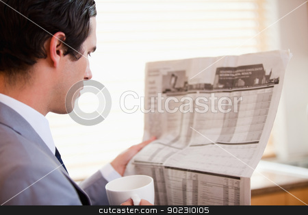 Side view of businessman reading newspaper stock photo, Side view of young businessman reading newspaper by Wavebreak Media