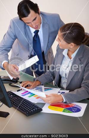 Businesswoman talking with her colleague about statistics stock photo, Young businesswoman talking with her colleague about statistics by Wavebreak Media