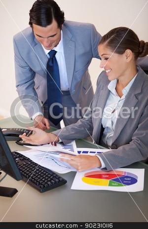 Business people working on diagrams together stock photo, Young business people working on diagrams together by Wavebreak Media