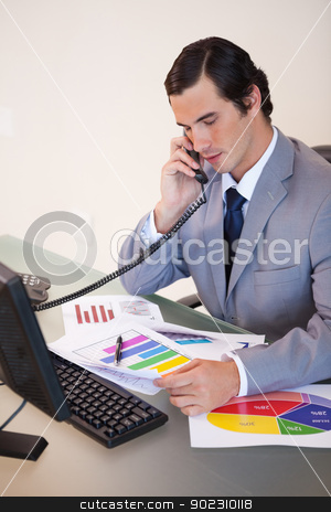Businessman on the phone talking about statistics stock photo, Young businessman on the phone talking about statistics by Wavebreak Media