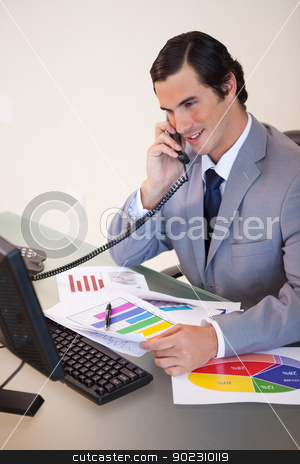 Smiling businessman talking about statistics on the phone stock photo, Smiling young businessman talking about statistics on the phone by Wavebreak Media