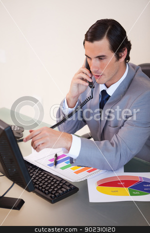 Businessman talking on the phone while working on statistics stock photo, Young businessman talking on the phone while working on statistics by Wavebreak Media