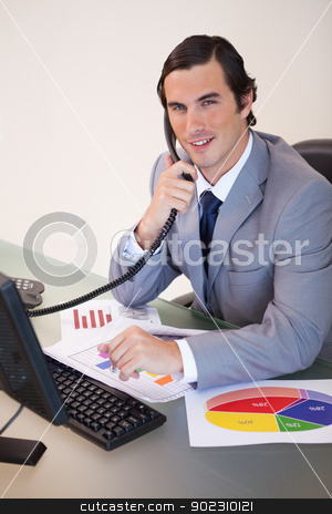 Smiling businessman on the phone working on statistics stock photo, Smiling young businessman on the phone working on statistics by Wavebreak Media