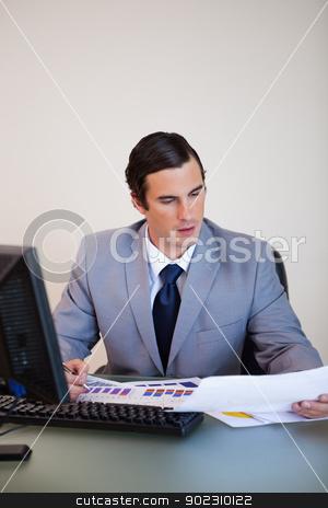 Businessman doing paperwork stock photo, Young businessman doing paperwork by Wavebreak Media