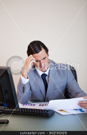 Businessman getting a headache from looking at paperwork stock photo, Young businessman getting a headache from looking at paperwork by Wavebreak Media