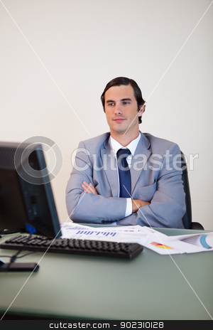 Businessman with arms folded waiting for his computer stock photo, Businessman with arms folded waiting for his computer to boot up by Wavebreak Media