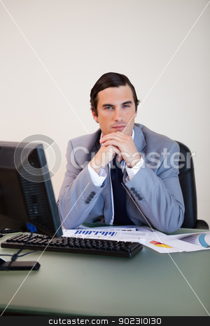 Businessman sitting behind his desk stock photo, Businessman in thoughts sitting behind his desk by Wavebreak Media