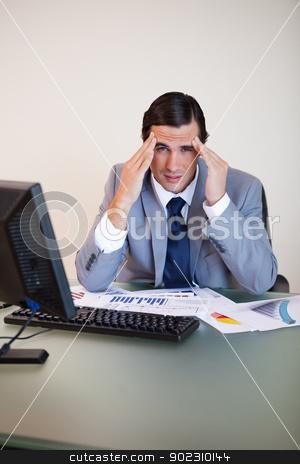 Businessman experiencing a headache stock photo, Businessman experiencing a headache at his desk by Wavebreak Media