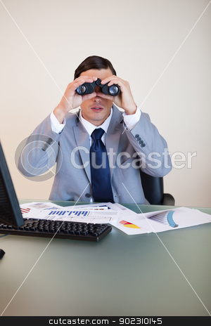 Businessman looking through binoculars stock photo, Young businessman looking through binoculars by Wavebreak Media