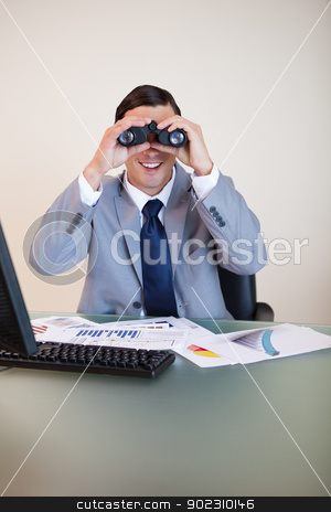 Businessman at his desk looking through binoculars stock photo, Smiling businessman at his desk looking through binoculars by Wavebreak Media