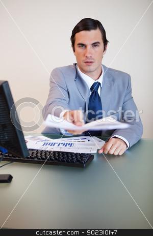 Businessman handing over contract stock photo, Businessman at his desk handing over contract by Wavebreak Media