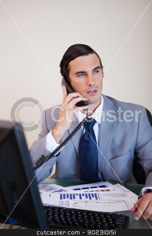 Businessman talking on the phone stock photo, Businessman at his desk talking on the phone by Wavebreak Media