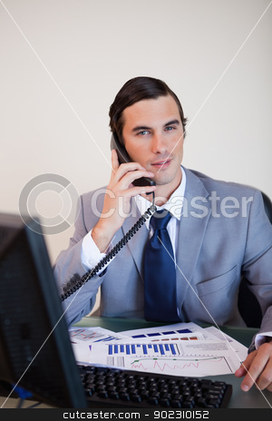 Businessman having a phone call stock photo, Businessman on his desk having a phone call by Wavebreak Media