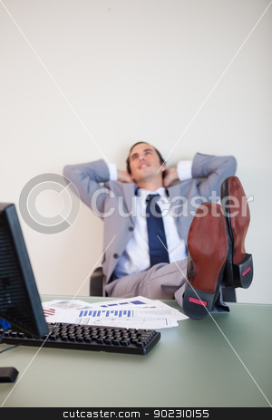 Feet being put up by businessman stock photo, Feet being put up on the desk by businessman by Wavebreak Media