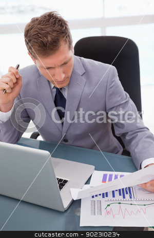 Businessman sitting at his desk stock photo, Businessman with statistics sitting at his desk by Wavebreak Media