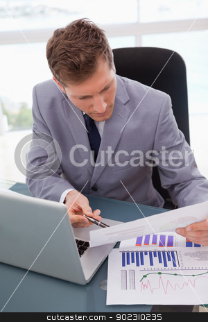 Businessman looking at statistics stock photo, Businessman at his desk looking at statistics by Wavebreak Media